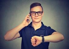 Uomo con l'orologio, parlante su un telefono che ha luogo in tempo per incontrarsi immagine stock libera da diritti