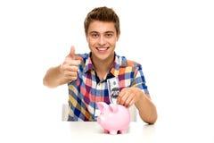 Uomo con la banca piggy che mostra i pollici in su Immagine Stock Libera da Diritti