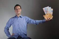 Uomo con la banconota dell'euro e del porcellino salvadanaio Fotografia Stock