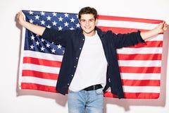 uomo con la bandiera degli Stati Uniti in mani su bianco Patriottismo di U.S.A. Fotografia Stock