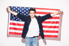 uomo con la bandiera degli Stati Uniti in mani su bianco Patriottismo di U.S.A. Immagine Stock