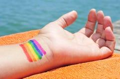 Uomo con la bandiera dell'arcobaleno dipinta in suo polso fotografia stock libera da diritti