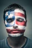 Uomo con la bandiera di U.S.A. sul fronte e sugli occhi chiusi Fotografia Stock