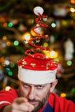 Uomo con la barba in cappello di Natale su fondo dell'albero fotografie stock libere da diritti