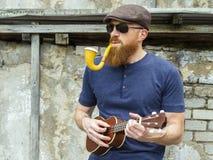 Uomo con la barba che gioca ukulele e che fuma un tubo Immagine Stock