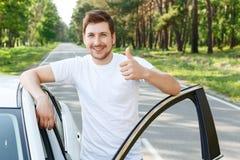 Uomo con la barba che sfoglia sull'automobile vicina fotografia stock libera da diritti