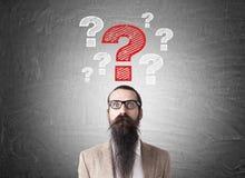 Uomo con la barba ed i punti interrogativi lunghi Fotografia Stock Libera da Diritti