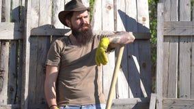 Uomo con la barba - manodopera agricola Strumenti di giardino Agricoltore che innaffia il germoglio sul campo Giorno di terra Bar video d archivio