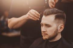 Uomo con la barba nel negozio di barbiere immagine stock