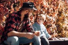 Uomo con la barba, pap? con il giovane figlio nel parco di autunno Il bambino ed suo padre sono nel parco di autunno immagini stock libere da diritti