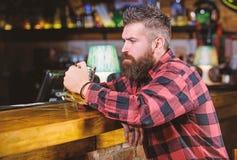 Uomo con la barba spendere svago nella barra scura Pantaloni a vita bassa che si rilassano alla barra con birra L'uomo barbuto de immagine stock libera da diritti