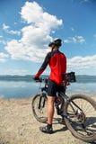 Uomo con la bici su un lago della montagna Fotografia Stock