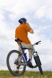 Uomo con la bicicletta che fa una chiamata di telefono Fotografia Stock