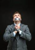 Uomo con la bocca coperta tramite il nastro protettivo Fotografie Stock