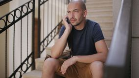 Uomo con la borsa che si siede sui punti delle scale e che parla sul telefono archivi video