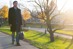 Uomo con la borsa sulla strada in parco Immagine Stock