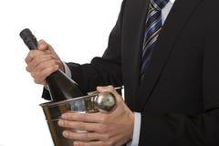 Uomo con la bottiglia del champagne del vestito in ghiaccio-secchio Fotografia Stock