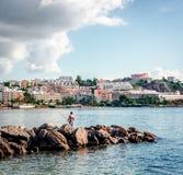 Uomo con la canna da pesca contro il townscape di Ibiza Immagini Stock