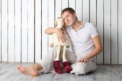 Uomo con la capra del giocattolo che si siede vicino alla parete Fotografia Stock Libera da Diritti