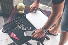Uomo con la cassa di lusso del computer portatile del pitone dello snakeskin su una tavola fuori del giardino asiatico Concetto d fotografia stock