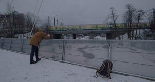 Uomo con la cellula che prende video del treno commovente nella città di inverno stock footage