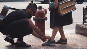 Uomo con la chitarra che lega la scarpa della ragazza nella via Coppie creative romantiche vicino alla spina rossa dell'idrante a stock footage