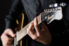 Uomo con la chitarra durante il concerto Immagine Stock