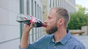 Uomo con la cola bevente della barba in città fotografia stock libera da diritti