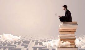Uomo con la compressa che si siede sui libri Fotografia Stock