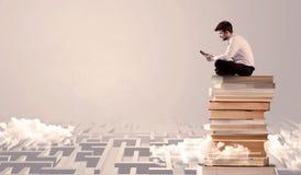 Uomo con la compressa che si siede sui libri Immagini Stock Libere da Diritti
