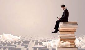 Uomo con la compressa che si siede sui libri Immagine Stock Libera da Diritti