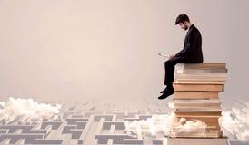 Uomo con la compressa che si siede sui libri Immagine Stock