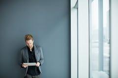 Uomo con la compressa dalla parete Fotografie Stock