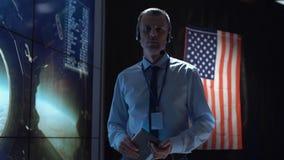 Uomo con la compressa nel centro di controllo della missione Immagine Stock
