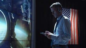 Uomo con la compressa nel centro di controllo della missione Fotografie Stock