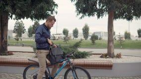 Uomo con la compressa su una bici stock footage