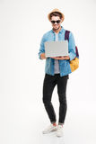 Uomo con la condizione dello zaino ed il computer portatile usando Fotografia Stock
