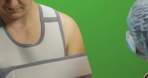 Uomo con la ferita sulla spalla Infermiere che controlla braccio Fasciatura per la spalla di riparazione archivi video