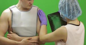 Uomo con la ferita sulla spalla L'infermiere esamina i raggi x Fasciatura per la spalla di riparazione archivi video