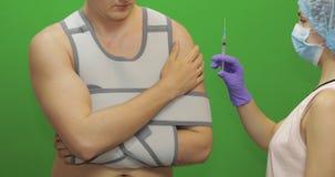 Uomo con la ferita sulla spalla L'infermiere fa la puntura da dolore Spalla della riparazione della fasciatura video d archivio