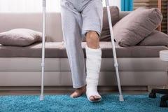 Uomo con la gamba rotta che si alza dal sofà fotografia stock libera da diritti