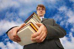 Uomo con la grande pila di libri contro il cielo Immagini Stock