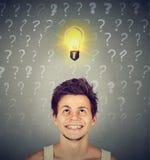 Uomo con la lampadina di idea e testa di cui sopra di molte domande Immagine Stock Libera da Diritti