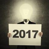 Uomo con la lampadina ed il numero 2017 Fotografie Stock Libere da Diritti