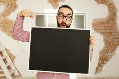 Uomo con la lavagna in bianco a disposizione che mostra con il dito Immagini Stock Libere da Diritti
