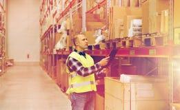 Uomo con la lavagna per appunti in maglia di sicurezza al magazzino Fotografia Stock Libera da Diritti