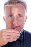 Uomo con la lente di ingrandimento di plastica piana - righello fotografie stock libere da diritti