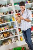 Uomo con la lista di controllo della borsa di drogheria in supermercato Fotografia Stock