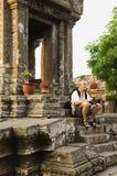 Uomo con la macchina fotografica digitale che si siede sui punti del tempio antico immagine stock