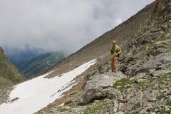 Uomo con la macchina fotografica in montagne. Fotografie Stock Libere da Diritti